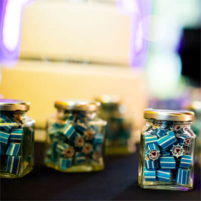 Personalised candy packaged into 80g square jars as a table setting for a wedding