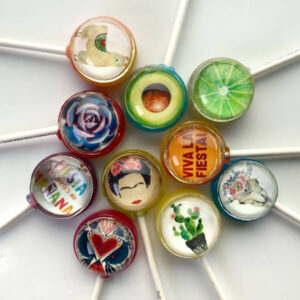 "Fiesta Pops, party inspired lollipops with edible image designs incl. Mexican painter Frida Kahlo, traditional textile love hearts, flowers, bull skulls, cactus, lamas, limes, avocado, ""Viva La Fiesta"" & ""Fiesta like there's no Manana""."
