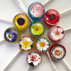 Spring flower images within a lollipop incl. Sunflower, Peony, Cherry Blossom, Lily, Daisy, Poppy, Rose, Violet, Frangipani, Daffodil.