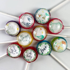 "Baby Pops are boy or girl themed baby shower lollipops with designs incl. elephants, stripped onesies, boy & girl mice, happy moons, a stalk carrying a new bundle of joy, baby foot prints, building blocks and cursive textile prints with ""love"", ""oh baby"" & ""Ready to Pop!""."